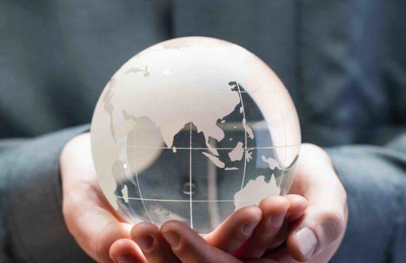 Hands holding model glass globe
